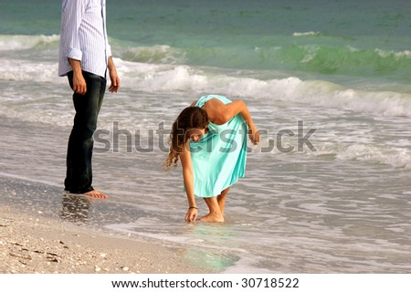attractive woman in dress stoops to pick up shell on beach as he male partner watches from the side  with waves crashing behind them at bonita beach in florida on the gulf of mexico - stock photo