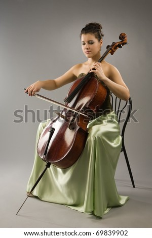 Attractive woman in evening dress playing cello - stock photo