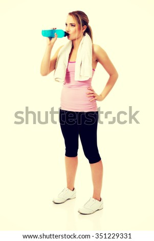 Attractive woman in fitness clothes drinking isotonic drink. - stock photo