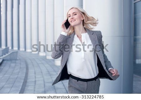 Attractive woman in formalwear is waiting for her business partner. She is talking on the mobile phone with him and looking forward with anticipation. The blond lady is standing and smiling - stock photo