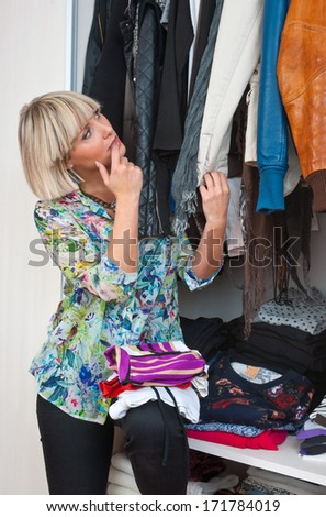 attractive woman in front of closet full of clothes - stock photo