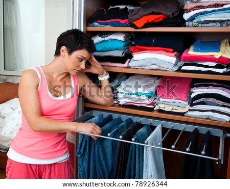 attractive woman in front of closet full with clothes thinking - stock photo