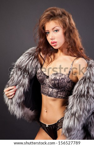Attractive woman in fur coat and bra. Shot in a studio on a black background