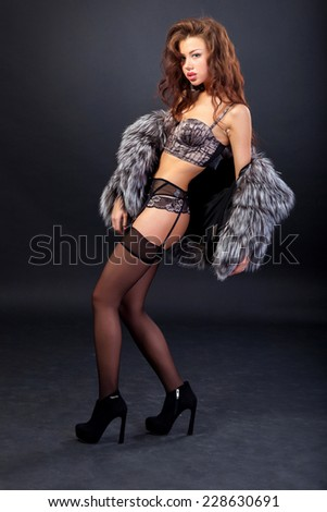 Attractive woman in fur coat and bra. Shot in a studio on a black background - stock photo