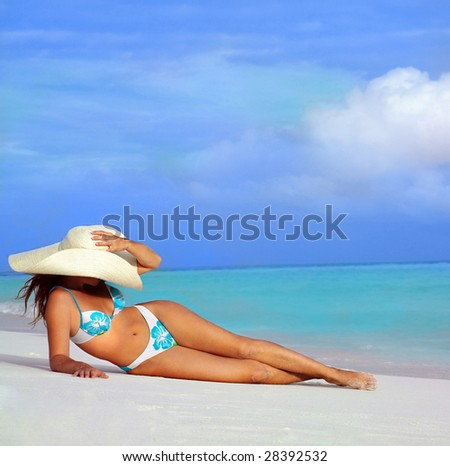 attractive woman in hat lying on the beach - stock photo