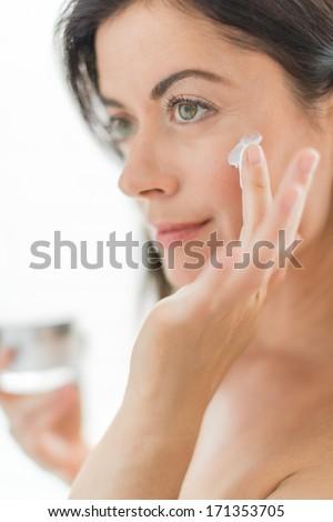 attractive woman in her forties applying cream - stock photo