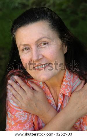 Attractive woman in her late fifties relaxing in her garden - stock photo