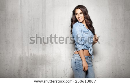 Attractive woman in jeans touching her hair - stock photo