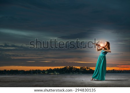 Attractive woman in long green dress playing violin - stock photo