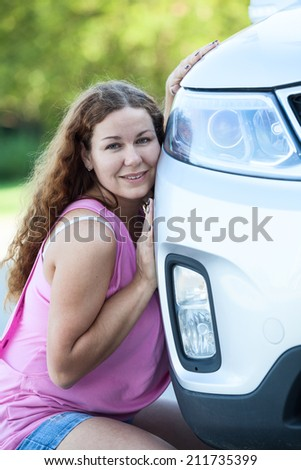 Attractive woman in pink blouse leaning her cheek to the car - stock photo