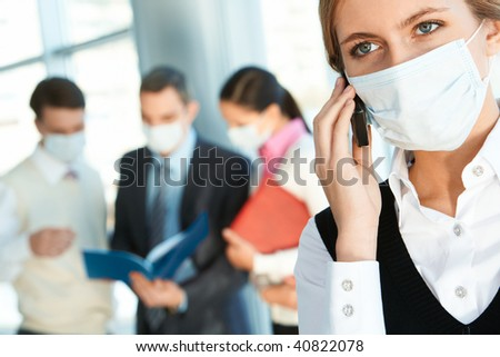 Attractive woman in protective mask calling somebody in working environment - stock photo