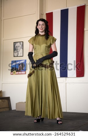 Attractive woman in 1940s clothing posing in front of flag during a reenactment of a World War II fashion show, Reading, PA held June 18, 2008 - stock photo