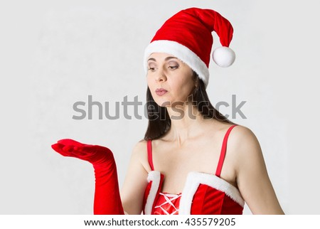 Attractive woman in Santa costume blowing at snowflakes. Background template - stock photo
