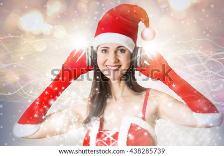 Attractive woman in Santa costume  with headset listening Christmas song  - stock photo