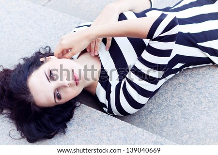 attractive woman in sexy dress in stripes sitting on stairs - stock photo