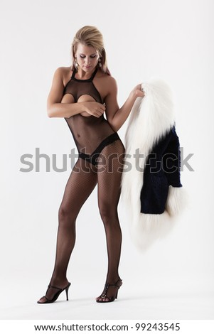 Attractive woman in sexy fishnet lingerie holding fur coat - stock photo