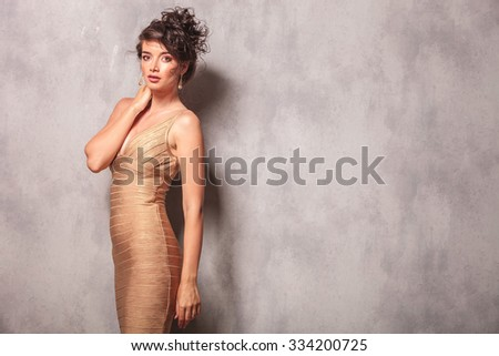 attractive woman in sexy golden dress pose standing while touching her neck