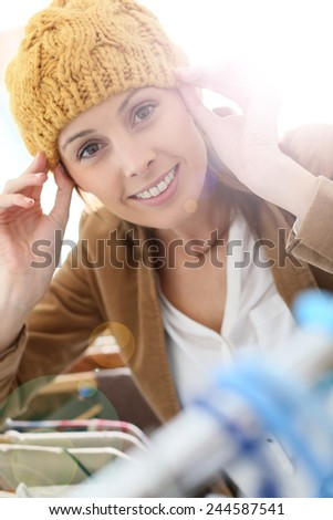 Attractive woman in store trying hat on  - stock photo