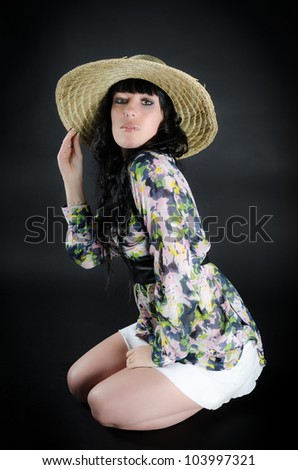 Attractive woman in straw hat posing on black background - stock photo
