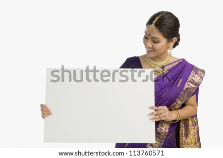 Attractive woman in traditional Assamese mekhla holding a blank placard and smiling - stock photo