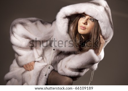 Attractive woman in white and gray fur coat with hood - stock photo