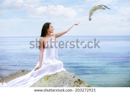 Attractive woman in white fabric on the rock - stock photo