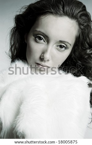 attractive woman in white furs over grey background