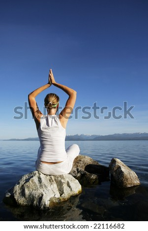 Attractive woman in white meditating by still water