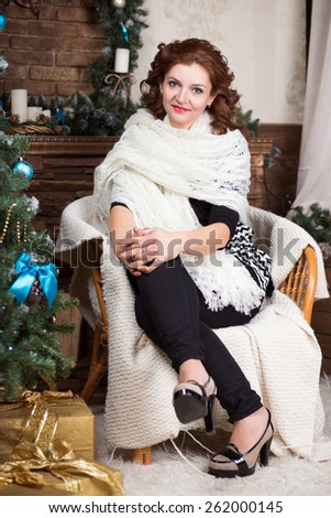 Attractive woman in white shawl sitting on the chair - stock photo