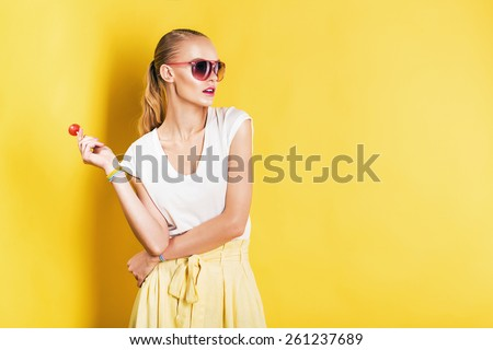 attractive woman in white top with lollipop in hand on yellow background - stock photo