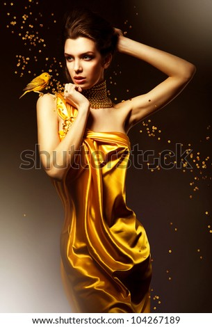 attractive woman in yellow dress with bird - stock photo