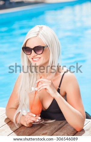 Attractive woman is drinking a cocktail in swimming pool. She is smiling and looking aside with joy. The lady is wearing sunglasses - stock photo