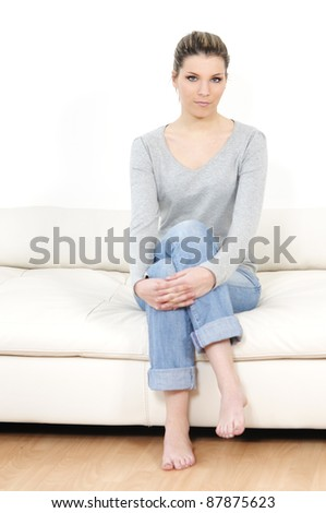 attractive woman is having a seat on a modern living room - stock photo
