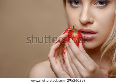 Attractive woman is holding a slice of strawberry in both her hands. She is touching it to her lips with desire. Isolated on brown background and there is copy space in left side - stock photo