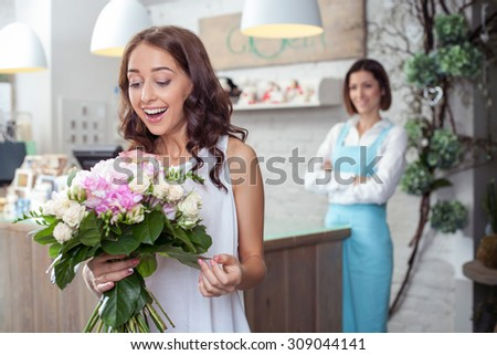 Attractive woman is holding beautiful flowers in store. She is looking at it with amazement and laughing. The florist is looking at her customer happily and smiling - stock photo