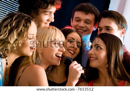 Attractive woman is holding the microphone and singing with friends
