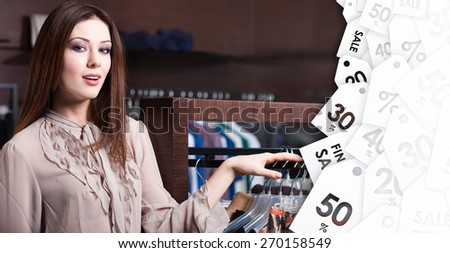 Attractive woman is in the store with wide range of clothes on sale - stock photo
