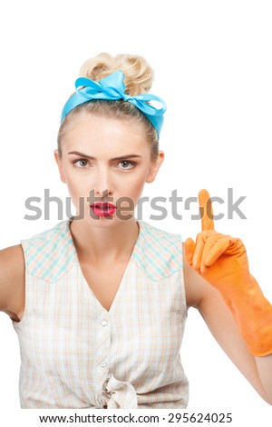 Attractive woman is pointing her finger with edification. She is looking at the camera seriously. She has orange rubber gloves on her hands. Isolated on background - stock photo