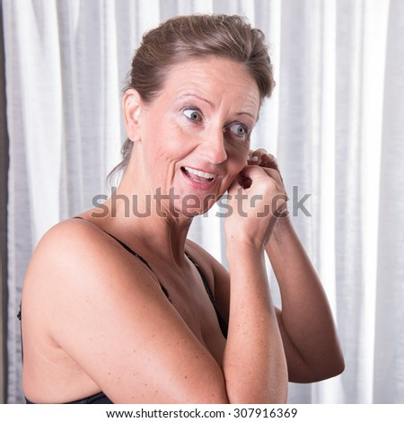 attractive woman is putting earring on