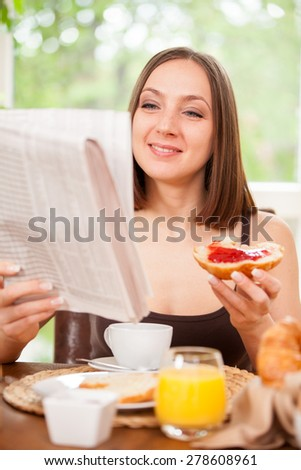 Attractive woman is reading the newspaper while having breakfast at home - stock photo