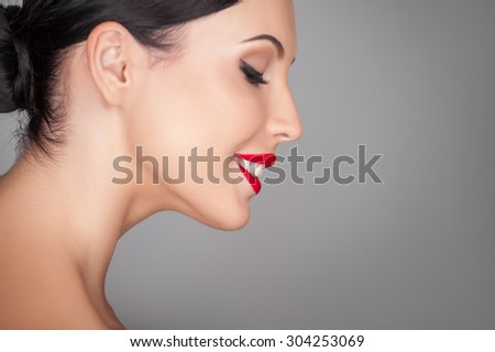Attractive woman is standing in profile and smiling. She is looking down shyly. The lady has perfect skin. Isolated and copy space in right side - stock photo