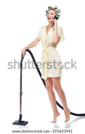 Attractive woman is talking on telephone and smiling. She is vacuuming her house. The girl has curlers in her hair. Isolated on background - stock photo