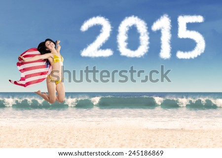Attractive woman jumping on beach while holding american flag, enjoying new year holiday - stock photo