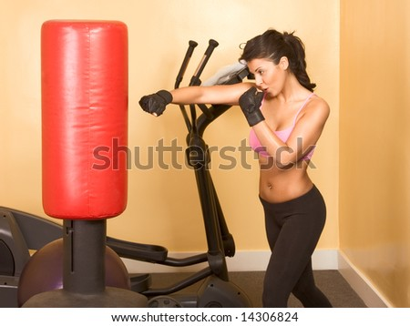 Attractive woman kickboxing using red punching bag - stock photo
