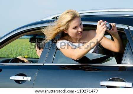 Attractive woman leaning out and photographing from the open rear car window with her hair blowing in the breeze