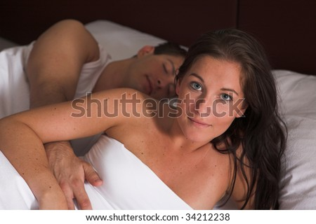 Attractive Woman lies in her bad while her partner is still asleep - stock photo