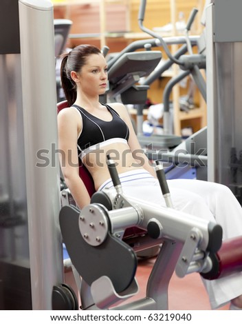 Attractive woman lifting weights with a leg press in the room of a sport centre - stock photo