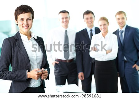 Attractive woman looking at camera and smiling against her business team - stock photo