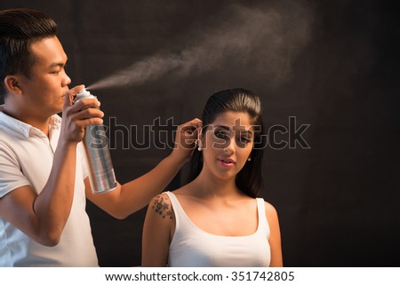 Attractive woman looking at camera when hairstylist spraying her hair - stock photo