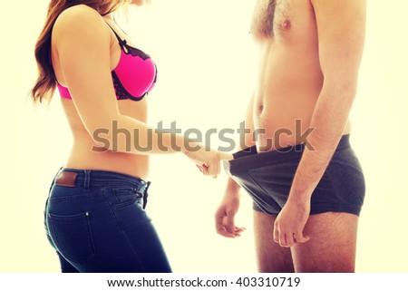 Attractive woman looking into man's panties. - stock photo